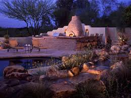 patio outdoor stone kitchen bar: outdoor entertaining area with grill and stone fireplace bar area with chairs pond with plants rocks and flowers nighttime view of outdoor room