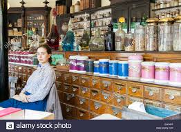 young female s assistant sitting down in victorian chemist stock photo young female s assistant sitting down in victorian chemist pharmacy at blists hill victorian town museum england uk