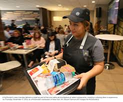 building a better experience just for you a mcdonald s crew member delivers a meal as part of the new table service feature at