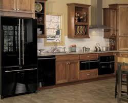 black and stainless kitchen kitchen designed with wooden kitchen cabinets and stainless steel hood with black appliances