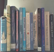 light blue books reading about winter ecology and climate history winter ecology books on my shelves