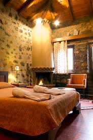 big master bedrooms couch bedroom fireplace: the stone and mortar walls exposed wood beams and rustic iron light fixtures make