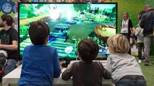 why integrate technology into the curriculum the reasons are facing a large monitor three elementary school aged boys play a video game