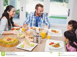 family dining table stock smiling family having food while discussing at dining table stock phot