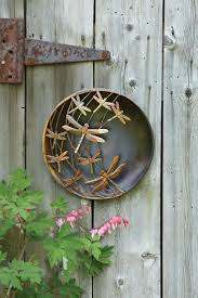 iron wall decor u love: dragonflies hover across this disc creating a dramatic piece of wall art the dragonflies have a textured surface and a hand applied finish