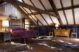 Picture of a beautiful room with lofted ceilings, wood detailing, wrought-iron bed frame and purple comforter