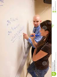 teacher helping student a math problem on a whiteboard stock teacher helping student a math problem on a whiteboard