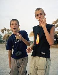 Two <b>young boys</b> holding cigarettes standing on the beach ...