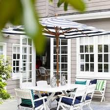 white striped patio umbrella: white x based outdoor dining table and white folding chairs