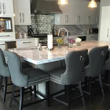 calacatta marble kitchen waterfall: amazing kitchen features white flat front cabinets paired with calcutta marble countertops and backsplash a