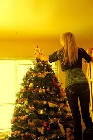File:Girl <b>Hanging Star</b> on Holiday <b>Christmas Tree</b> - Photo by D ...