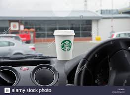 starbucks logo stock photos starbucks logo stock images alamy starbucks coffee to go in a takeaway paper cup on a car dashboard in a motorway