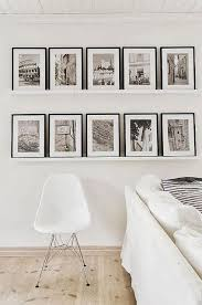 white living room with framed black and white photos on floating shelves black white home office cococozy 5