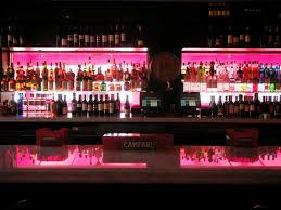red lighting illuminates the back of the bar bar lighting ideas