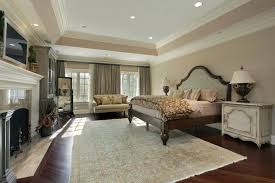 big master bedrooms couch bedroom fireplace: a spacious bedroom with hardwood floors and a stately fireplace two large windows are inset