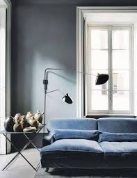moody living room vignette with gray walls blue velvet sofa and black double swing cb2 swing arm brass wall