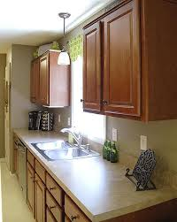 pendant lamp as the lighting for a kitchen sink light cream kitchen counter wood cabinetry above sink lighting