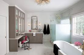 bathroom features gray shaker vanity: a pocket door opens to a gray master bathroom filled with gray shaker vanity cabinets adorned with brass pulls topped with mirrored cabinets