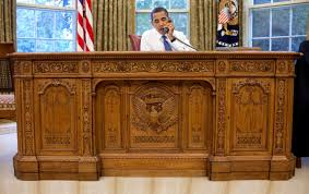 barack obama sits behind the heavy and ornate wood resolute desk bill clinton oval office rug