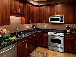 cherry wood kitchen cabinets with silver appliances and black countertops brown solid wood furniture