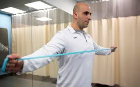 discipio uses a resistance band to work his shoulders robin lubbockwbur band office cubicle