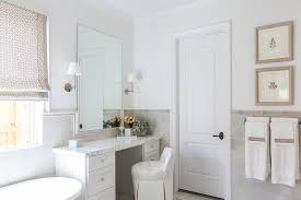 bathroom features gray shaker vanity: white and gray bathroom features white paint on upper walls and gray tiles on lower walls lined with a make up vanity topped with white marble paired with a