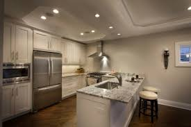 recessed lighting spacing kitchen above backless bar stools with round seat cushions covered by cream vinyl baseboard lighting