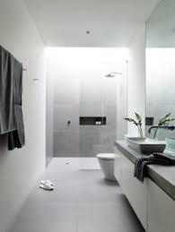a modern bathroom in a light color pallet featuring light gray tile and a slightly curved ample shower lighting