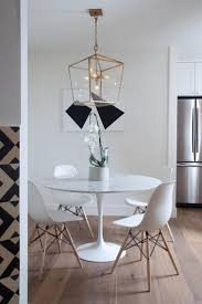 chair dining tables room contemporary: white eames style dining chairs surround the contemporary round dining table in this minimalist dining room wide plank european oak wood flooring ground