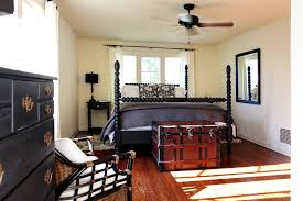 farmhouse bedroom example of a country bedroom design in los angeles with white walls and medium black bedroom furniture hint