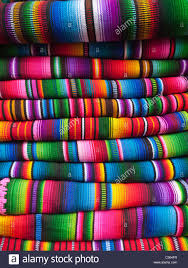 colorful blankets woven in a traditional manner are stacked up