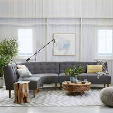 apartment living room with mid century modern style decor paired modern tufted sofa sleeper and geometric patterned area rug also wooden rectangle center add midcentury modern style