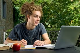 make the most of summer with essay contest scholarships   the    a teenager sitting outside writing on his computer