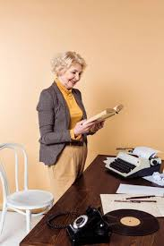 Smiling senior <b>woman reading</b> book near table with rotary phone