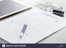 business man signing his resignation letter on his desk before business man signing his resignation letter on his desk before sending to his boss to quit a job resignation letter information digital tablet a
