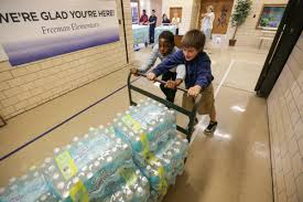 flint water crisis a visual essay water water everywhere man elementary sixth graders kashif nance left and john orr team up in 2015 to push a cartload of donated water being distributed to various