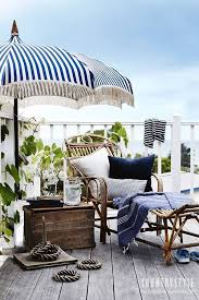 white striped patio umbrella: a navy and white striped umbrella rattan chaise old wooden chest