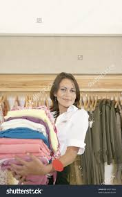shop assistant holding a pile of clothes in a fashion store stock save to a lightbox