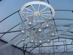 mason jar chandelier made with wagon wheel for the wedding alternating length wagon wheel mason jar