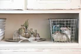 rustic hutch dining room: on the open shelf i simply tossed a couple of silver acorns in with my basket of vintage mason jars and added some faux evergreen clippings and a pretty