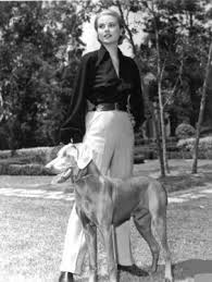 Grace Kelly in slacks and shirt with one of her dogs