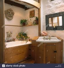 washstand bathroom pine: pine panelling on bath and built in basin in small cottage bathroom with painted white stone