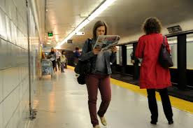 photo essay commute krysten mccumber a w passes the time waiting for the next train by reading the daily newspaper at