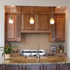 beech wood kitchen cabinets: a large wood hood cabinet is surrounded by fluted columns in a rustic