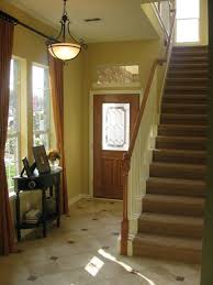 lighting gorgeous entry hall lighting ideas using wrought iron chandeliers with warm white lamps over black brown fabric lighting