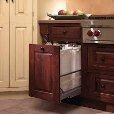 trash cans default: decorative  wooden decorative kitchen trash cans under brown granite countertop near large white cabinet on cream marble kitchen flooring