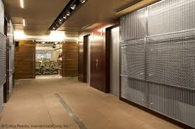 the contrast of the wood and sparkle of the architectural mesh create a unique back drop banker office space