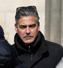 George Clooney has revealed his unusual new mustache on the set of his latest movie The Monuments Men in Berlin yesterday (March 24). - george-clooney