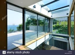 large sliding patio doors: large sliding glass doors open floor to ceiling glass panels a low profile building in a seaside location