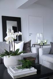 day orchid decor: white bowl of orchids on coffee table on top of large coffee table book vessel can be fuller with more flowers
